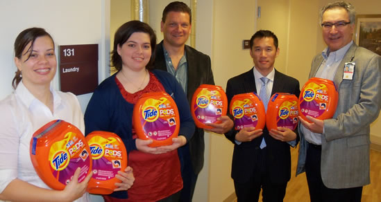5 people stand holding containers of Tide Pods.
