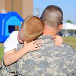 A servicemember holds his young son.